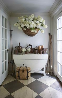 Nora Murphy country house entry with checkerboard pattern flooring, white dropleaf table, and huge basket of hydrangea and collection of copper watering cans. Nora Murphy Country Style to Inspire! Country Style Homes, Cottage Style, Farmhouse Style, Farmhouse Decor, French Farmhouse, Modern Farmhouse, Painted Wood Floors, Country Decor, Country Style Furniture