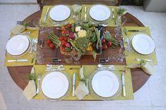 Para esta mesa, elegemos jogos americanos em palha amarela, sousplats transparentes, sobre os quais foram dispostos pratos em louça limoges branca. Descansos de talher em forma de legumes garimpados durante uma viagem à Parise marcadores de lugar em forma de lousa da Antropologie.