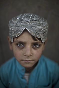 Afghan refugee Hasanat Mohammed, 5, poses for a picture while standing outside his home in a poor neighbourhood on the outskirts of Islamaba...