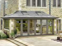 Modern grey conservatory attached to a stone house with wood decking in front of it