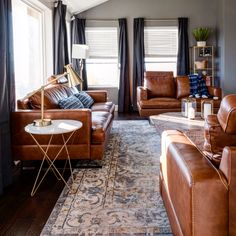 Mid century living room , Carmel leather couches dark gray curtains drapes, gray walls, marble side tables. sleek and cool