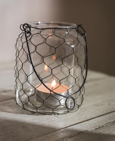 Chicken-wire wrapped jar as votive candle holder with wire handle, posted by Ana Rosa Votive Candle Holders, Candle Lanterns, Diy Candles, Candle Jars, Candle Containers, Mason Jar Crafts, Mason Jars, Chicken Wire Crafts, Colored Sand