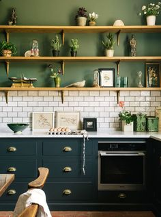 Our dated kitchen is 25 years old, but we don't have the funds for a total re-do. The countertops need to stay... What color should the cabinets be? Image via DeVOL kitchens - lovely green cabinetry and creamy white subway tile, plus beautiful shelf styling