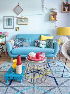 Salón con sofá en color azul y complementos en colores