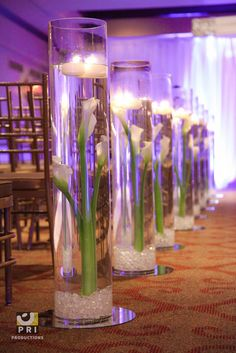 4 foot tall glass floral aisle ends. Glass cylinder with acrylic rocks, calla lilies and floating candles.