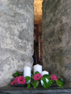 an alcove at Priston Mills decorated with candles and hot pink gerbera heads and ivy, very simple but very effective!