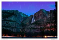 Winter Yosemite Falls at night with star trails and car trails. Yosemite National Park