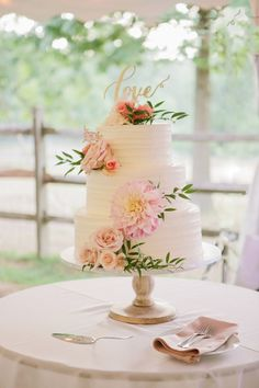 Cute white wedding cake with flowers and love topper