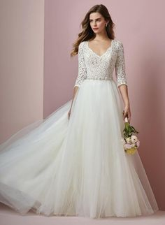 01fb6bd5f37ebc Rebecca Ingram Designer romantic wedding dress features an allover lace  bodice with three-quarter sleeves