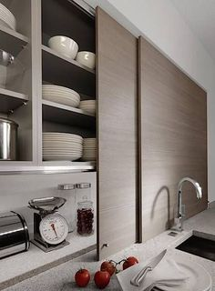 Thin sliding cabinet doors in a kitchen by Germany company Beeck Kuchen conceal countertop clutter. | Beek Kuchen Sliding Kitchen Cabinets | Remodelista