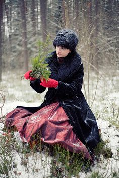Woman gathering evergreen branches in snowy field