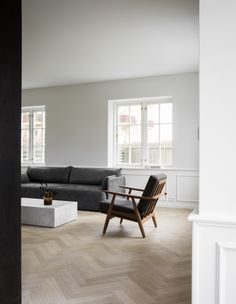 Dark mid-century teak furniture and marble pieces, set against a white background.