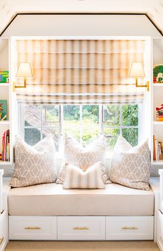 Fabulous attic kids' room features a built-in window seat reading nook with drawers below topped with gray geometric pillows under window dressed in white and gray stripe roman shade with built-in bookcases on either side illuminated by Architectural Wall Sconces filled with toys and books.