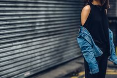 Anisa Sojka styles black Chicuel cold shoulder top | Fitted flared cropped trousers | Miu Miu cat eye sunglasses | Blue denim jacket | Ankle boots with a heel | Straight shoulder length brunette hair | Fashion blogger street style shot in London by Moeez Ali