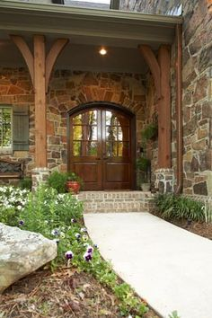 I like the combo of brick and stone here and the posts and the wooden door