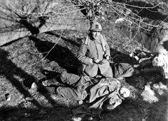 An Italian officer kneeling near an Austrian soldier fallen in a battle on the Piave front Veneto 1918