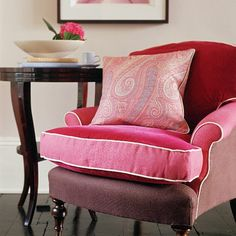A William Yeoward two-tone pink armchair has piping for a smart finish, while a paisley de Le Cuona cushion provides pattern. Dark polished floorboards, a glossy JVB side table and the frame on a floral print add contrast. :: Chair - William Yeoward ::   Table - JVB :: Cushion - de Le Cuona  Picture - Meyers at Artefact :: Cup and saucer - BC Pottery