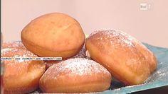 Per i bomboloni: 250 g di farina manitoba, 250 g di farina 0, 150 g di zucchero semolato, 25 g di lievito fresco, 125 ml di latte tiepido, la scorza di un limone, 80 g di burro, sale, 125 ml di acqua Per la crema pasticcera: 1/2 lt di latte, 160 g di zucchero, 80 g di farina, 4 tuorli, 1 stecca di vaniglia, zucchero a velo Procedimento In una ciotola, mettiamo il latte tiepido e sciogliamo all'interno il lievito di birra; uniamo lo zucchero e l'acqua a temperatura ambiente. Profumiamo con la