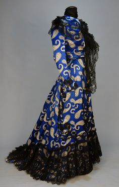 PRINTED SATIN TRAINED HIGH NECK AFTERNOON GOWN, c. 1902. 2-piece black dotted sapphire blue silk with white paisleys of varying sizes having black and blue dots, boned bodice trimmed in black embroidered net with sequins and bowknot appliques on sleeve, skirt having appliques, ruffled hem with non-conforming lace over ruffle, cotton lining.