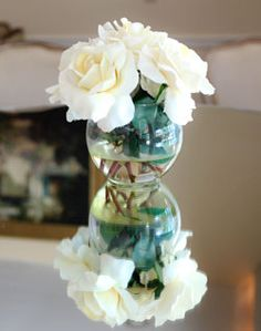 Super tiny white centerpiece with three roses, put on top of a mirror with some candles? Maybe an larger centerpiece in the same exact style and two of the mini centerpieces on the sides with votives?