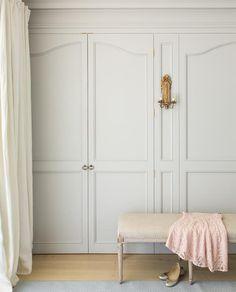 Chic, French closet feature slight gray wardrobe closet doors illuminated by a gold leaf sconce alongside a cream linen French bench.