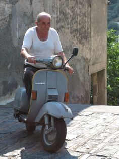 Italian man driving around the corner in Taormina (Godfather scenery)