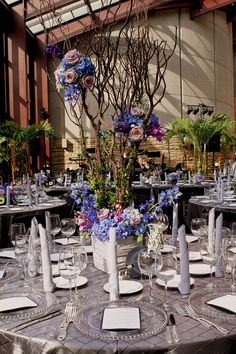 centerpieces: trees constructed of Manzanita, with blue hydrangea, roses, delphium, waxflower, and orchids with beautiful and full white peonies.