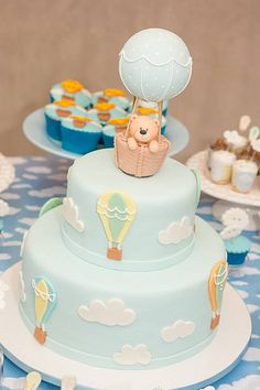 A super cute hot air balloons with two layers baby shower cake with teddy bear topping. Baby Cakes, Fondant Baby Torte, Torta Baby Shower, Teddy Bear Baby Shower, Baby Boy Shower, Baby Boy Birthday Cake, Hot Air Balloon Cake, Baby Shower Balloons, Cute Cakes