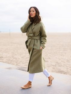 Aimee Song wears an olive green wrap coat, cuffed white jeans, and nude ballet flats