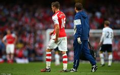 Aaron Ramsey of Arsenal holds his leg as he walks off the pitch after picking up an injury...