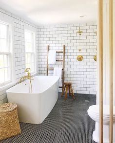 White Subway tile bathroom with brass and black hex tile floor | House Seven