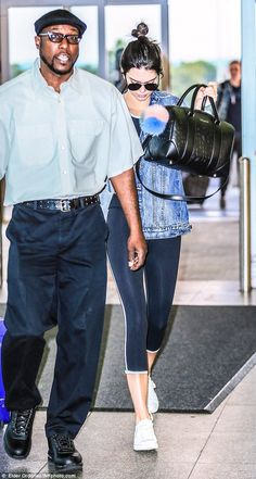 Making light work of things: Accompanied by a male aide who transported her luggage, Kendall carried her essentials in a stylish black leather handbag