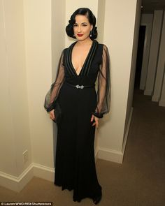 Surgically-enhanced bust: Dita Von Teese took the plunge in a black sheer-sleeved gown at the Kilian x Loree Dinner in Los Angeles on Tuesday