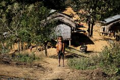 A boy stands on the edge of a village, home to the hidden tribe that enjoy a simple lifest...