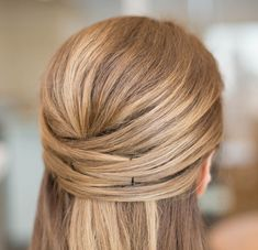 Use bobby pins to create a quick half up 'do. See 23 other life-changing styling hacks that make having a good hair day easy.