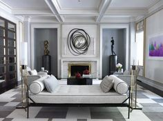 A sleek sitting area with coffered ceilings showcases modern art, placed in alcoves that flank the fireplace.
