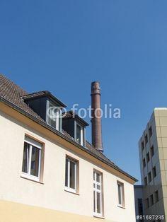 Fabrikschornstein hinter einem Wohnhaus mit Fassade in Beige in Bielefeld-Schildesche in OWL