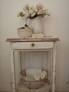"Old white ""chippy"" stand with drawer and shelf...love the look of the porcelain pitcher with creamy flowers adorning the top."