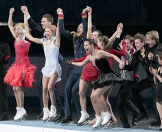 The Russian team wave to spectators as they stand on the podium during the flower ceremony after placing first in the team figure skating co...