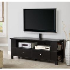 Put the finishing touch on your home entertainment center with this black wood TV stand with mount. This stand offers space for your electronic components, and the attached bracket allows you to securely mount a flat-screen TV up to 60 inches.