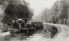 "Caption: "" Black and white photograph taken from the towpath, shows the Fellows, Morton & Clayton Limited steamer (No 214) with 2 boatmen sat on the cabin. There are men visible on the opposite side of the canal"""