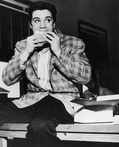 Elvis Presley eating a sandwich. | 21 Awesome Vintage Photos Of Celebrities Eating