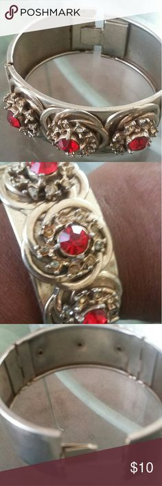 Gold tone metal bangle with faux ruby stones Vintage gold metal bangle with floral design. Faux ruby accent stones. Snap clasp closure. Very good vintage condition. Late 1950s, early 1960s Jewelry Bracelets