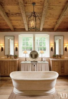 A limestone tub stands in the center of a master bath in a Connecticut poolhouse