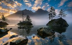 Just before dawn the sun rises over the Hintersee National park in Austria. The mist clears over the dead calm lake giving a mystic view of the mountains greeting the morning sun. Like a land untouched by human hand the quietness and peace is tangible in the delicate shades and majestic nature rising from the night, Photograph by Gregor Thelen
