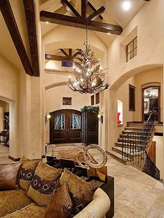 Large Foyer In Adobe Home With Cathedral Wood-Beamed Ceilings, Deer Antler Chandelier and Sitting Area. #HomeStratosphere