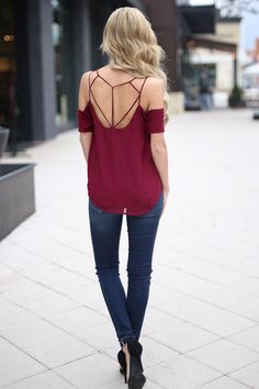 """Wine, scoop neck, cold shoulder top with short sleeves and strappy back detail. Semi-sheer fabric. 100% Polyester. Hand wash cold.Lightweight material, not stretchy. Tasha is 5'5, size 2, 25"""" waist, 32D and is shown wearing a small. *Fit is true to size. Get the Look: Purse, Jeans, Heels Stylist Suggestion: Backless"""