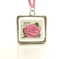 This soldered glass pendant necklace features a postage stamp with a bright pink rose between glass salvaged from a broken window. The pendant hangs from a silky cord in a coordinating shade of pink.