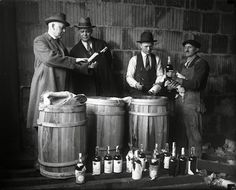 Prohibition helped the rise of gangsters like Al Capone, who ran hooch and illegal drinking dens. Here cops inspect some of the alcohol Capone and his associates were running.