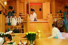 Shinto priests and miko, dressed in heian robes, performing the chrysanthemum festival rituals.